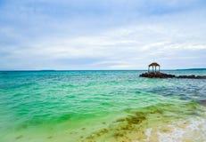 Capanna tradizionale sulla roccia del mare in mezzo all'oceano calmo nell'aria fresca di mattina immagine stock
