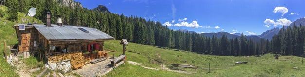 Capanne circondate dalle alte montagne, alpi italiane Fotografia Stock