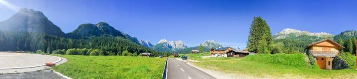 Capanne circondate dalle alte montagne, alpi italiane Immagini Stock