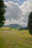 Capanne della montagna nei prati in un giorno soleggiato con cielo blu con le nuvole, dolomia, Italia Fotografia Stock Libera da Diritti