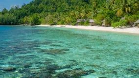 Capanne di bambù sulla spiaggia, Coral Reef di un alloggio presso famiglie Gam Island, Papuan ad ovest, Raja Ampat, Indonesia Fotografia Stock