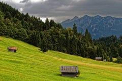 Capanne di legno alla collina verde in alpi bavaresi alla caduta Fotografie Stock Libere da Diritti