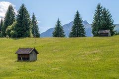 Capanne su un prato davanti ad una montagna Immagini Stock