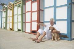 Capanne variopinte della spiaggia ed uomo senior con il cane Fotografia Stock Libera da Diritti