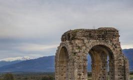 Caparra曲拱与在底层多雪的山的,卡塞里斯,西班牙 免版税库存照片