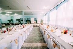 Capas blancas decorativas y cintas coloreadas en sillas en la tabla festiva fotografía de archivo libre de regalías