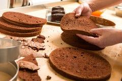 Capas de la torta del corte del cocinero y amontonamiento de ellos fotos de archivo