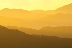 Capas nebulosas de rangos de montaña durante salida del sol fotos de archivo libres de regalías