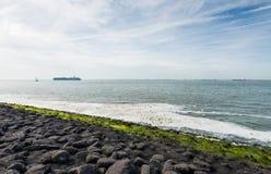 Capas negras, verdes y blancas en la costa Imagenes de archivo