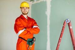 c53af387f81 Capataz alegre en ropa de trabajo anaranjada y el casco de protección  amarillo feliz foto de