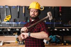 1e0ac793728 Capataz en el casco de protección amarillo que sostiene lo disponible del  martillo cuidadosamente fotografía de