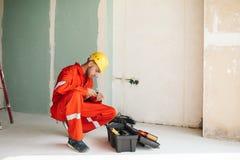 7a217f7da00 Capataz en la ropa de trabajo anaranjada y el casco de protección amarillo  cuidadosamente c imagen