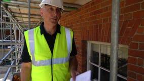 Capataz, topógrafo, trabajador o arquitecto de sexo masculino del constructor trabajando en solar de la construcción almacen de metraje de vídeo