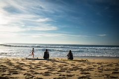 Capbreton, Франция - 4-ое октября 2017: задний взгляд серферов девушек женщин сидя на песчаном пляже на surfboard Стоковые Изображения RF