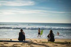 Capbreton Francja, Październik, - 4, 2017: tylny widok kobiet dziewczyn surfingowowie siedzi na piaskowatej plaży na surfboard Obrazy Stock