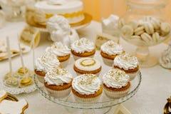 Capcakes με την άσπρη κρέμα και χρυσά μπιζέλια σε ένα πιάτο γυαλιού Στοκ Φωτογραφία