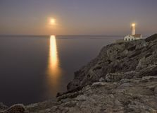Capdepera φάρος στο σούρουπο, με τη φεγγαροαχτίδα στη θάλασσα και τους βράχους, Μαγιόρκα, Ισπανία στοκ εικόνες