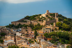 Capdepera castle on green hill in Mallorca. Island, Spain. Beautiful landsacape with medieval architecture, green trees and blue sky with clouds on a sunny day Royalty Free Stock Photo