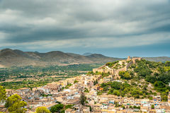 Capdepera castle on green hill in Mallorca. Island, Spain. Beautiful landsacape with medieval architecture, green trees and blue sky with clouds on a sunny day Stock Photos