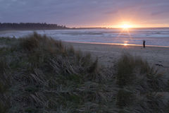 Cape Arago Sunset. A lone figure on the beach takes a picture of the scene as the sun sets over Cape Arago State Park, Oregon stock image