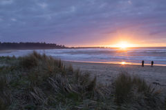 Cape Arago Sunset. Two figures on the beach take pictures of the scene as the sun sets over Cape Arago State Park, Oregon royalty free stock photo