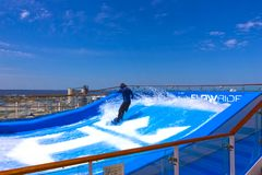 Cape Canaveral, USA - APRIL 29, 2018: Man surfing on the FlowRider aboard the Oasis of the Seas by Royal Caribbean. Cape Canaveral, USA - APRIL 29, 2018: Man Stock Image