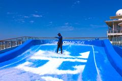 Cape Canaveral, USA - APRIL 29, 2018: Man surfing on the FlowRider aboard the Oasis of the Seas by Royal Caribbean. Cape Canaveral, USA - APRIL 29, 2018: Man Royalty Free Stock Image