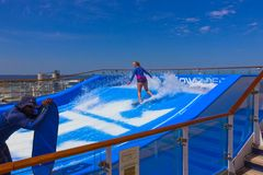 Cape Canaveral, USA - APRIL 29, 2018: Woman surfing on the FlowRider aboard the Oasis of the Seas by Royal Caribbean. Cape Canaveral, USA - APRIL 29, 2018: Woman Royalty Free Stock Image