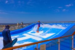 Cape Canaveral, USA - APRIL 29, 2018: Woman surfing on the FlowRider aboard the Oasis of the Seas by Royal Caribbean. Cape Canaveral, USA - APRIL 29, 2018: Woman Royalty Free Stock Photos