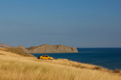 Cape Chameleon. Yellow car on the Bay in the background of Cape Chameleon Stock Photography