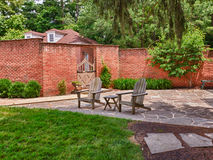 Cape cod chairs on stone patio. Wooden cape cod style chairs on crazy paving patio in front of brick wall and garden gate Stock Images