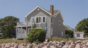 Cape Cod Home. Cape cod Massachuttes style dream home on a beautiful day along the sea Stock Photography