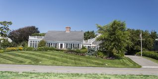Cape Cod Home. Cape Cod Massachuttes style dream home on a beautiful day along the sea Royalty Free Stock Images