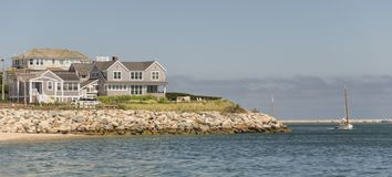 Cape Cod Home. Cape Cod Massachuttes style dream home on a beautiful day along the sea. Beautiful sailing boat crossing the channel stock photography