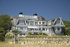 Cape Cod Home. Cape cod Massachuttes style dream home on a beautiful day along the sea Stock Photos