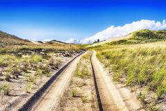 Cape Cod National Seashore Nature. Tire tracks leading through the sand dunes on the Cape Cod National Seashore in Truro Massachusetts on a sunny blue sky day royalty free stock photography