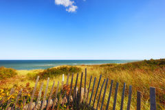 Cape Cod Shoreline in Truro, Massachusetts. Seaside view of Highland light beach on Cape Cod in Massachusetts.  Fencing borders the sea grass growing on low sand Stock Photos