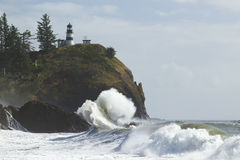 Cape Disappointment Lighthouse. A lighthouse on a cliff with large crashing waves Royalty Free Stock Images