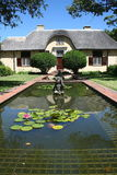 Cape Dutch house behind reflecting pond. Leg of lamb gabled Cape Dutch style house with reflecting pond in front and cherub in pond stock photos