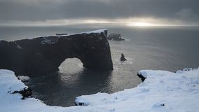 Cape Dyrholaey, Iceland. Panoramic image of the coastal landscape of Cape Dyrholaey on a winter day with snow-covered coastline, Iceland stock image