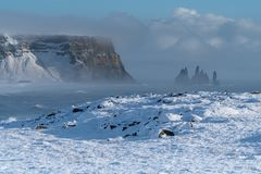 Cape Dyrholaey, Iceland. Panoramic image of the coastal landscape of Cape Dyrholaey on a winter day with snow-covered coastline, Iceland stock photography