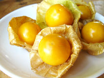 Cape gooseberry. Or golden berry & x28;Physalis peruviana& x29;. Delicious fruit for health in a white plate on wooden table stock photo