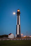 Cape Henry Lighthouse. At dusk with a full moon lit in the background. This landmark lighthouse is one of the oldest in the USA. It was built of cast iron in Royalty Free Stock Photos