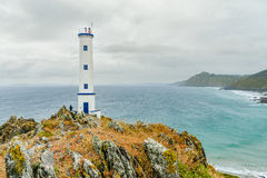 Cape Home lighthouse in Cangas do Morrazo. Cape Home lighthouse in foreground with the Atlantic Sea behind it in a cloudy day Royalty Free Stock Photography