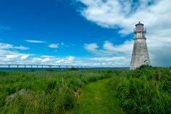 Cape Jourimain Lighthouse. A mowed path leads you to the lighthouse through the wild meadow with the Confederation Bridge to PEI in the background. Cape stock photography