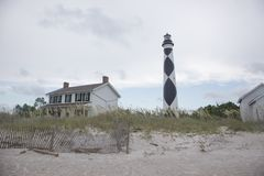 Cape Lookout Lighthouse and Sand Dunes. Cape Lookout National Seashore, North Carolina - a broken wood fence and light keepers house stand near the iconic light Stock Image