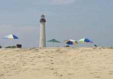 Cape May Lighthouse View. A view of the Cape May lighthouse from the beach with umbrellas in the foreground Stock Photos