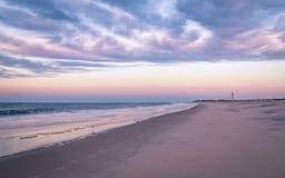 Cape May, NJ, fyr, strand och hav i violetta toner på soluppgång royaltyfri foto