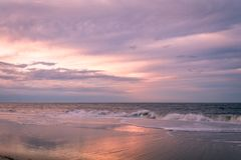 Cape May, NJ, strand och hav i violetta toner p? soluppg?ng arkivfoto
