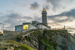Cape Mayor lighthouse in Santander. With a cloudy sky, during the sunset and with stairs goingdown the cape Royalty Free Stock Photo